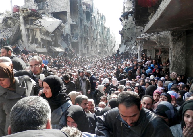 This picture from Jan 2014 shows Palestinian Refugees of the besieged Yarmouk refugee camp queuing to receive food supplies in Damascus, Syria.
